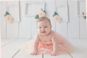 A cute and beautiful girl crawling on white floor while smiling