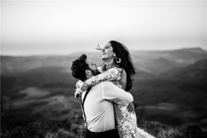 A man and woman hugging near hill