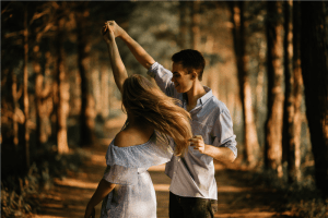 Photo of a man and a woman dancing at center of trees