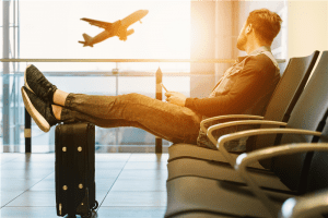 Photo of a man sitting on gang chair with feet on luggage looking at airplane