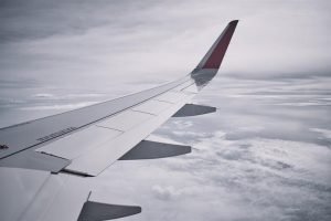 Airplane wing in a cloudy sky