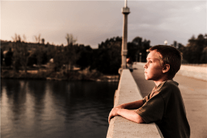 Photo of boy at the bridge near body of water