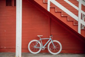 A white bicycle next to a red wall
