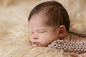 baby inside of beige and brown cloth photo