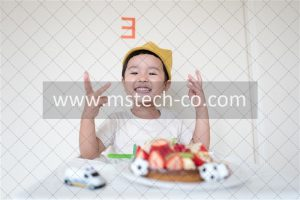 boy in front of cake and white car toy photo