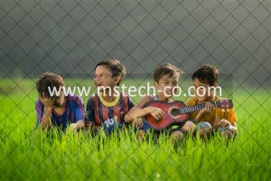 four boys laughing and sitting on grass during daytime phot