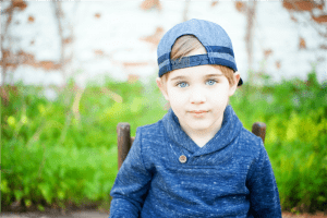 boy in blue knit sweater and blue denim cap photo