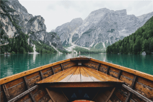 brown wooden boat moving towards the mountain photo