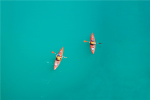 two person kayaking on open body of water photo