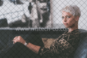 woman sitting on sofa holding eyeglasses photo